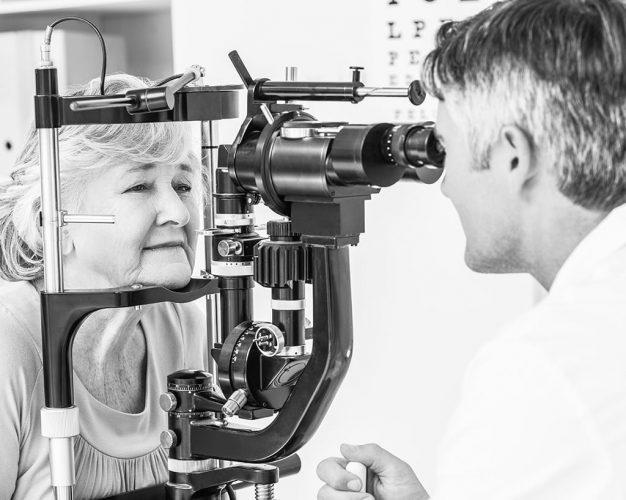 Optician examining senior female patient through slit lamp